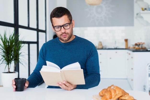 man reading a romance novel at home