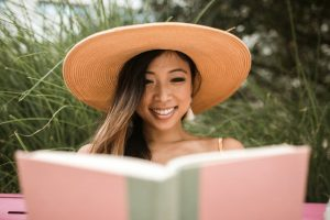 A woman reads a romance novel, smiling at the mix of emotions and feelings.