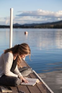 woman-reading-novel-by-lake