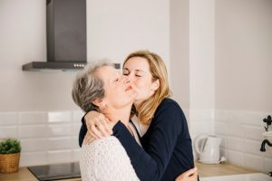 a mother and daughter embracing in a kitchen